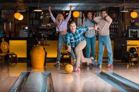 handsome young man throwing bowling ball near excited multicultural friends