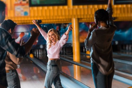 Photo pour Excited blonde girl showing winner gesture while standing near bowling alley with multicultural friends - image libre de droit