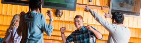 Photo pour Plan panoramique d'amis multiculturels excités souriant et montrant des gestes gagnants au bowling club - image libre de droit