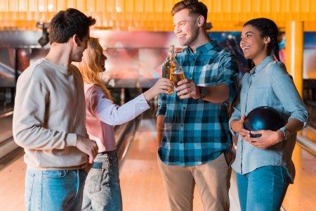 Foto de Feliz amigo multicultural hablando y tintineo botellas de cerveza en el club de arco - Imagen libre de derechos