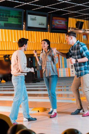 excited african american girl showing winner gesture near happy multicultural friends in bowling club