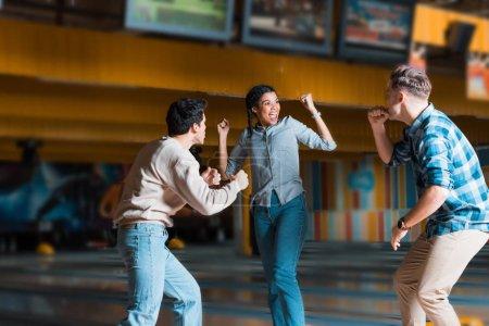 Photo pour Excité afro-américaine fille avec ami multiculturel montrant des gestes gagnants au bowling club - image libre de droit