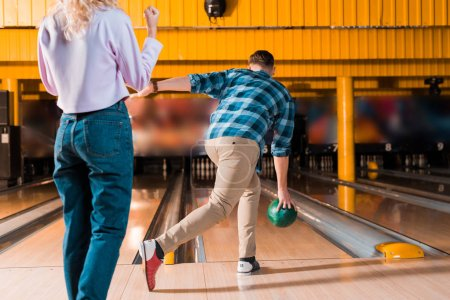cropped view of girl standing near man throwing bowling ball on skittle alley
