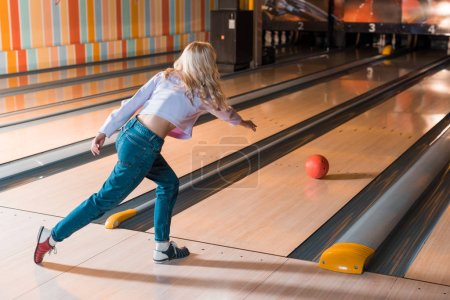 Photo pour Young blonde salope throwing bowling ball on skittle alley - image libre de droit