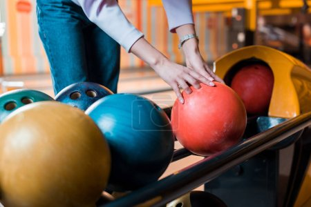 cropped view of young woman choosing bowling ball