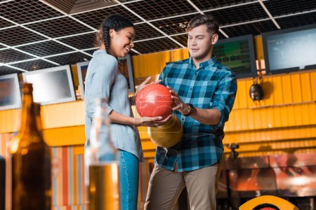 selective focus of handsome man showing bowling ball to smiling african american girl
