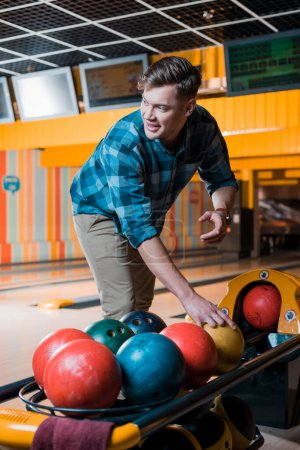 handsome smiling man taking bowling ball in bowling club