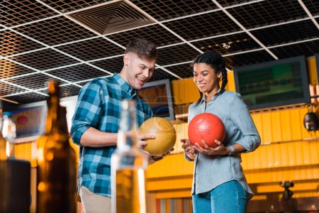 selective focus of interracial couple talking and smiling while holding bowling balls