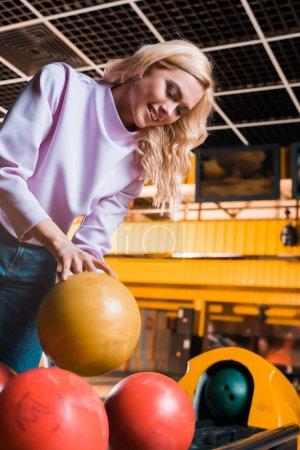cheerful blonde girl taking bowling ball in bowling club