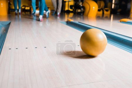 selective focus of bowling ball on skittle alley and friends standing on background