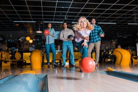 Photo pour Souriant fille blonde lancer boule de bowling sur allée de skittle près d'amis multiculturels - image libre de droit