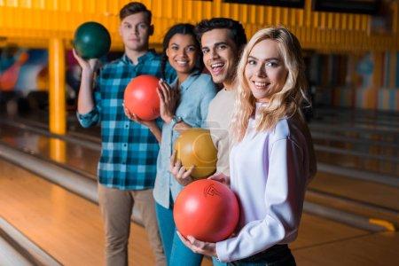 Photo pour Heureux amis multiculturels tenant des boules de bowling et regardant la caméra tout en se tenant dans le club de bowling - image libre de droit