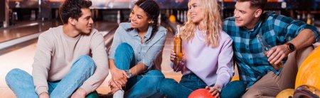 Photo pour Photo panoramique d'amis multiculturels heureux avec des bouteilles de bière assis et parlant sur une piste de quilles dans un club de quilles - image libre de droit