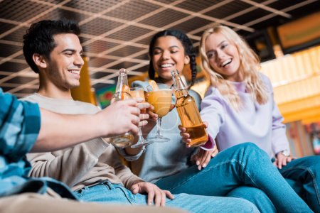 Photo for Cheerful multicultural friends clinking with bottles of beer and cocktail glasses while sitting in bowling club - Royalty Free Image