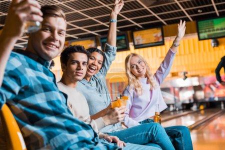 Photo pour Des amis multiculturels souriants à la caméra alors qu'ils sont assis dans un club de quilles avec des cocktails et de la bière - image libre de droit