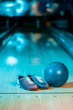 selective focus of bowling shoes and ball on bowling alley