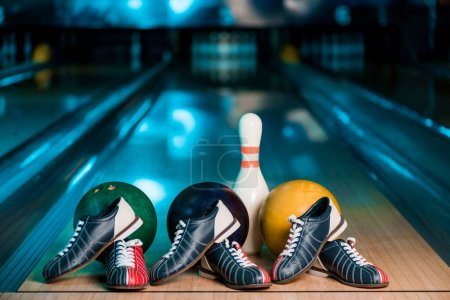 Photo for Selective focus of bowling shoes, balls and skittle on skittle alley in bowling club - Royalty Free Image