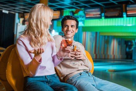 Photo pour Couple joyeux parler tout en étant assis dans le club de bowling et de boire des cocktails - image libre de droit