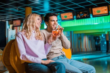 cheerful couple looking away and smiling while drinking cocktails in bowling club