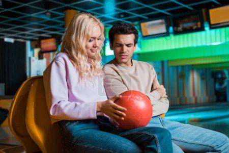 Photo pour Fille souriante montrant boule de bowling à petit ami réfléchi dans le club de bowling - image libre de droit