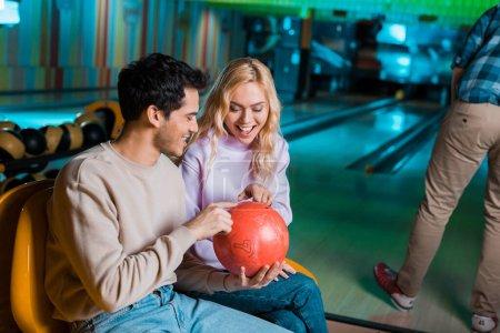 Jubelnde Männer und Frauen, die im Bowlingclub beim Bowling Ball schauen