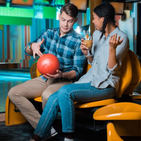 lächelnde Afroamerikanerin mit einem Glas Cocktail, während ihr Freund eine Bowlingkugel zeigt