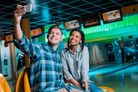 smiling interracial couple taking selfie on smartphone while sitting in bowling club