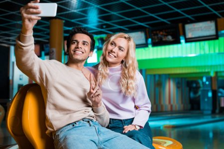 Photo for Happy young man showing victory gesture while sitting in bowilng club and taking selfie with smiling girlfriend - Royalty Free Image