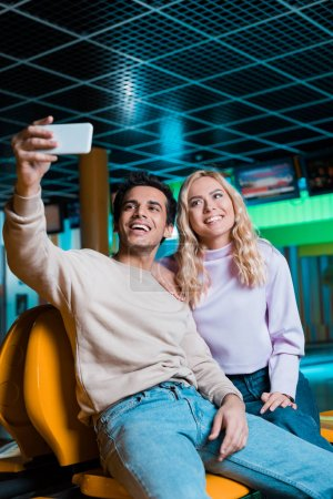 cheerful couple taking selfie on smartphone while sitting in bowling club