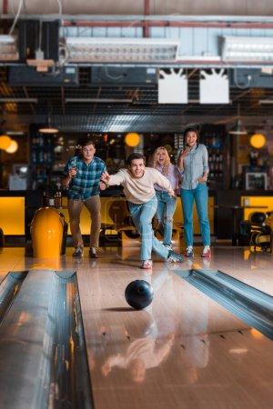 Photo pour Beau jeune homme lançant la boule de bowling sur l'allée de skittle près des amis multiculturels - image libre de droit