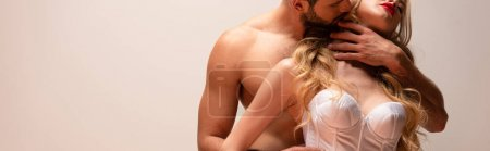 Photo for Panoramic shot of bearded and muscular man kissing sexy woman isolated on grey - Royalty Free Image