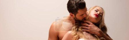 Photo pour Plan panoramique de bel homme musclé embrassant femme sexy isolé sur gris - image libre de droit