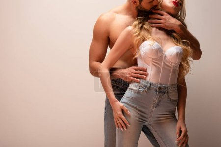 cropped view of muscular man hugging sexy woman isolated on grey