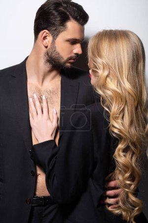 handsome bearded man hugging beautiful woman on white