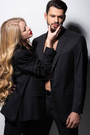 Photo for Beautiful woman touching face of bearded man on white - Royalty Free Image