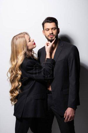 Photo pour Belle jeune femme touchant le visage de l'homme barbu sur blanc - image libre de droit