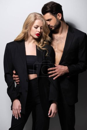 bearded man hugging attractive girlfriend with red lips on white