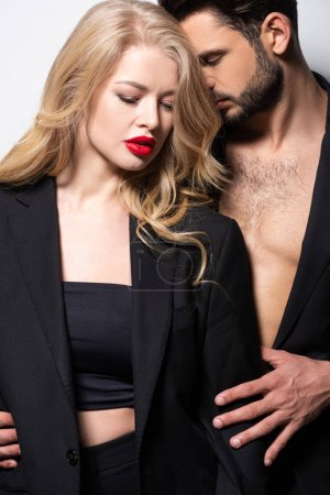 Photo for Bearded man embracing attractive girlfriend with red lips on white - Royalty Free Image