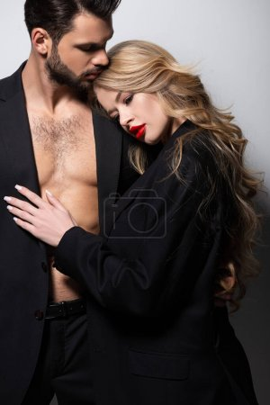 Photo for Beautiful young woman touching muscular man on white - Royalty Free Image
