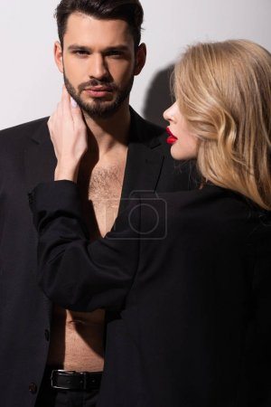Photo pour Séduisante femme aux lèvres rouges touchant homme barbu sur blanc - image libre de droit