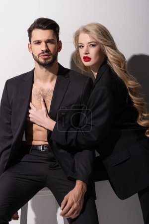 Photo for Beautiful woman with red lips touching handsome man on white - Royalty Free Image