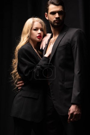 Photo for Attractive woman standing with bearded man isolated on black - Royalty Free Image
