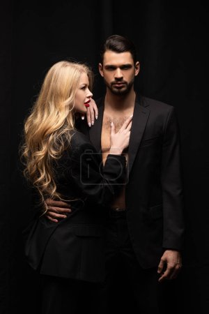 attractive curly woman touching handsome man isolated on black