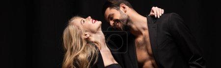 Photo pour Plan panoramique de l'homme heureux regardant femme gaie isolé sur noir - image libre de droit