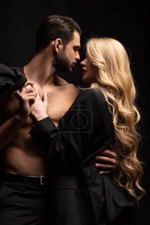 young woman and sexy muscular man looking at each other isolated on black