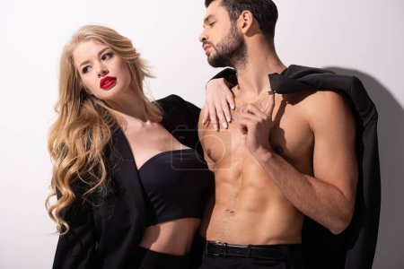 Photo for Young stylish woman standing with sexy muscular man on white - Royalty Free Image