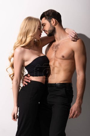 Photo for Side view of stylish woman standing with sexy shirtless man on white - Royalty Free Image
