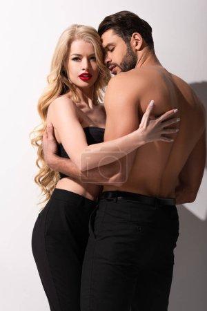 Photo pour Homme torse nu embrassant belle fille sur blanc - image libre de droit