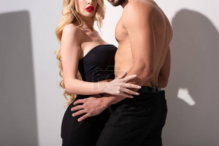 Photo for Cropped view of shirtless man hugging girl on white - Royalty Free Image