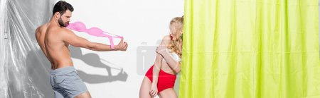 Photo for Panoramic shot of playful man holding bra and teasing pin up girl on white - Royalty Free Image